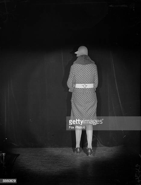A woman walking away from the camera with a torch lamp around her waist