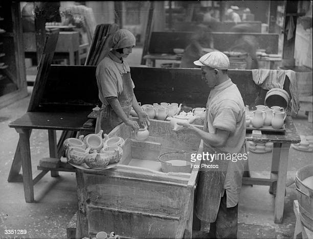 Production line workers dipping pots in to a vat of glaze at the Wedgwood pottery Stoke On Trent Staffordshire