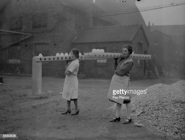 Two women balancing large trays of pots on their shoulders as they carry them across a yard at the Wedgwood pottery Stoke On Trent Staffordshire