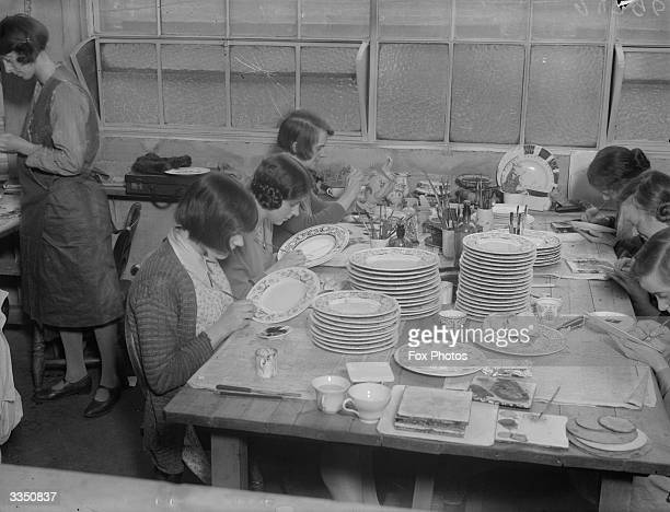 Women painting decoration on to plates by hand at the Wedgwood pottery Stoke On Trent Staffordshire