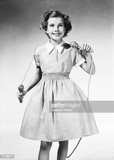 A young girl in a summer frock with smocking at the waist 3 button placket opening at the neck and a full skirt The pointed collar and cuffs on the...