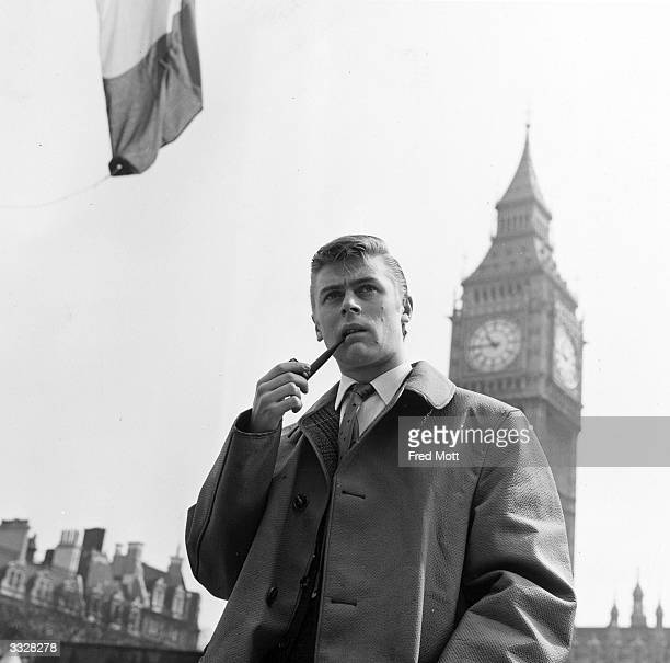 Comedian Mike Yarwood smoking his pipe in front of Big Ben's clocktower London
