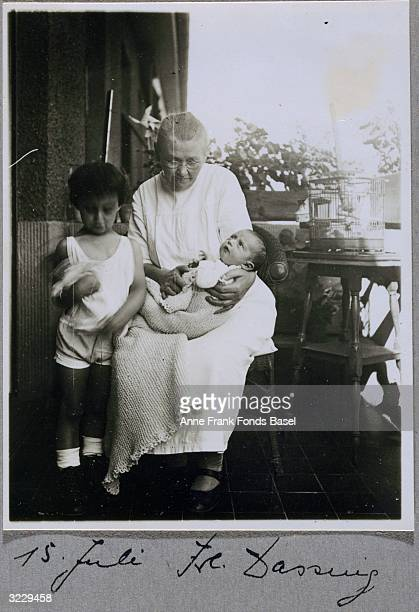 EXCLUSIVE Mrs Dassing holding Anne Frank on her lap with Anne's sister Margot standing beside them Frankfurt am Main Germany They are next to a bird...