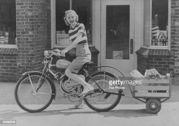 Young woman riding a lightweight power bicycle called a 'Whizzer' which pulls a trailer containg shopping. The trailer can be detached for use as a...
