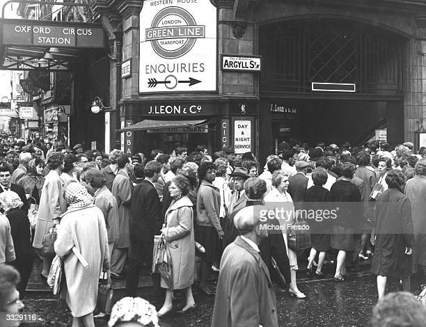 Crowds of people outside Oxford Circus underground station on the corner of Oxford Street and Argyll Street London