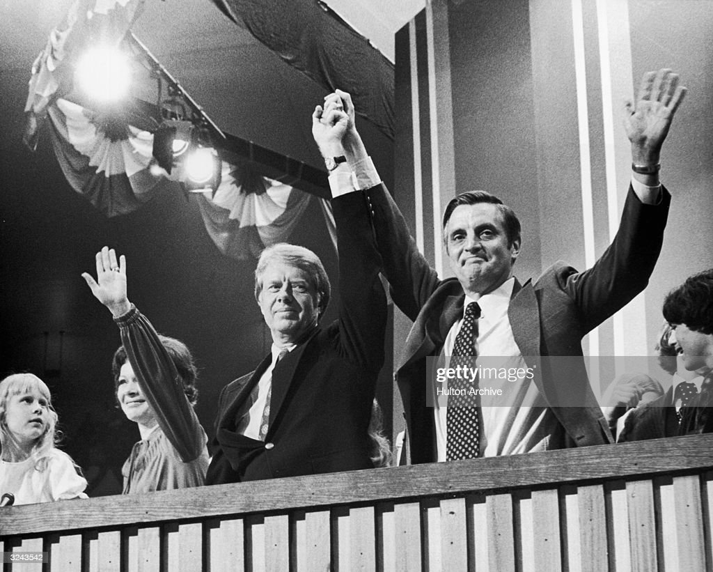 Democratic Presidential nominee Jimmy Carter raises hands with Vice Presidential nominee Walter Mondale (right) at the Democratic National Convention, New York City. Carter's wife, Rosalynn, and their daughter Amy, wave beside them.
