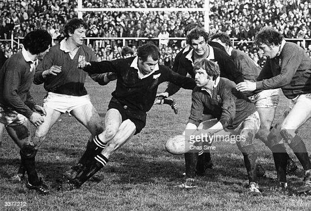 Derek Quinnell of the British Lions passes the ball as New Zealand's Lawrie Knight closes during an international test at Lancaster Park Christchurch...