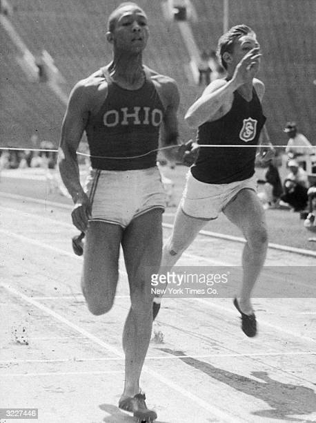 Fulllength image of American track and field athlete Jesse Owens breaking the ribbon while crossing the finish line winning the 100yard dash for Ohio...