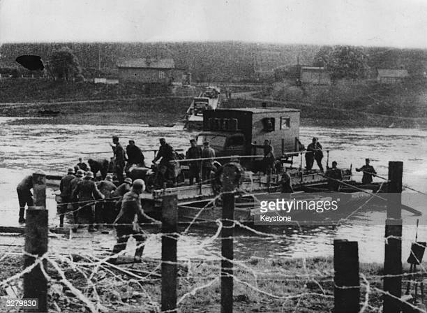 Hindered by the dynamited bridge German troops cross the river at Maastricht in boats