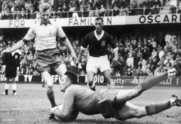 Goalkeeper Kalle Svensson assisted by full back Sven Axbom saves a shot from John Charles during Sweden's World Cup match against Wales in Gothenburg...