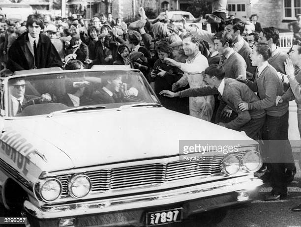 Workmen and schoolchildren mob the car carrying British pop sensation The Beatles from Adelaide airport during their Australian tour
