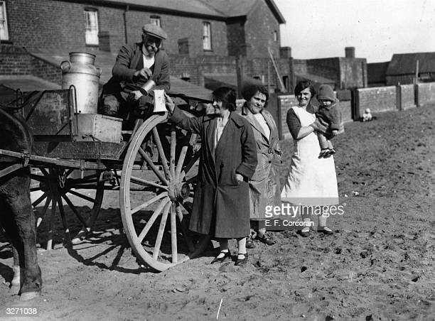A milkman in Yorkshire during his round in a horsedrawn cart pours milk into a customer's jug