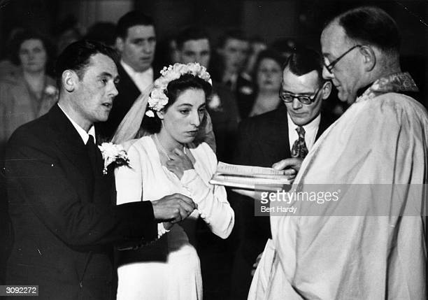 An East End couple Alfred Whitbread and Ellen Newman making their marriage vows in font of the vicar of St Andrew's Bethnal Green London Original...