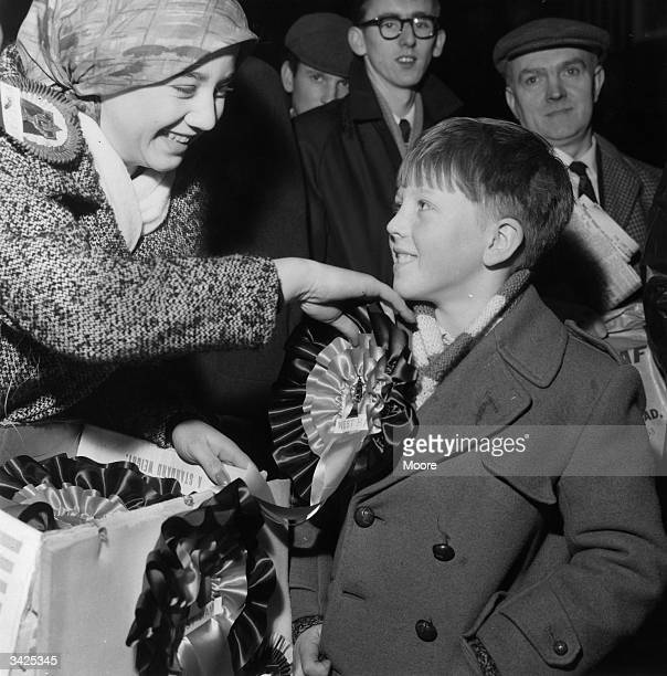 Maureen Swilley pins a rosette on young West Ham United supporter, Graham Farquahar, at St Pancras, as fans set off to see the FA Cup semi-final with...