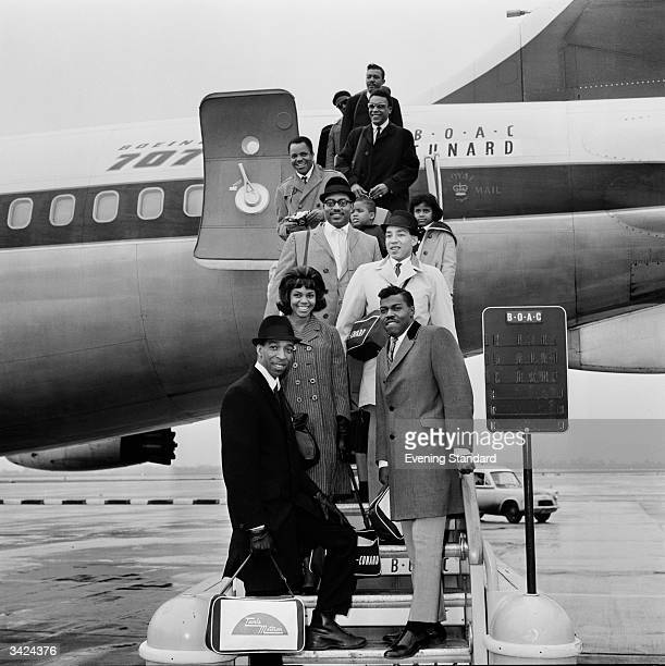 Soul pop singer and songwriter Smokey Robinson front and his band The Miracles who include Smokey's wife Claudette disembarking from an aeroplane...