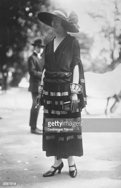 A model wearing an outfit designed by Madeleine Vionnet including a pair of ornate gloves