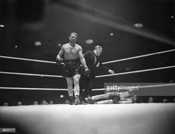 RussianAmerican boxer Gus Lesnevich turns away as the referee begins to count Freddie Mills out during their world cruiserweight championship fight...