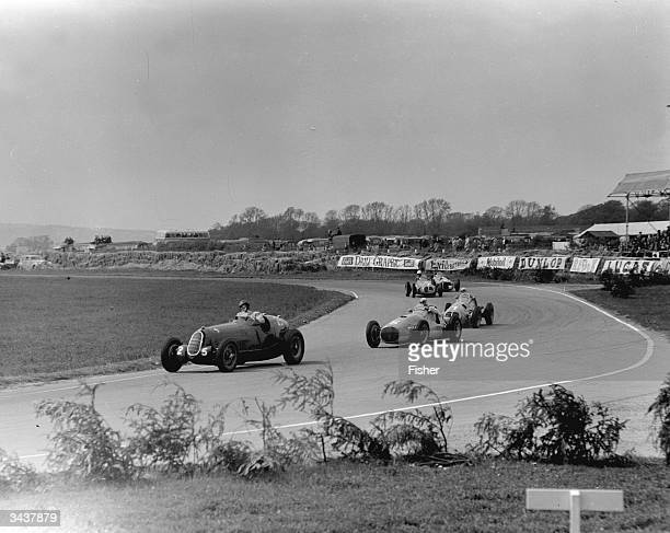 D Poore in an Alfa leading B Bira in an Osca and G Farina in a Maserati at Woodcote Corner during the Festival of Britain race Goodwood