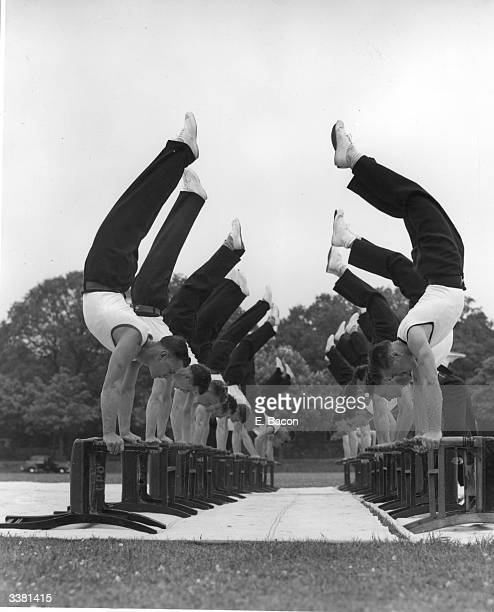 The Combined Services gymnastics team forming a chair balancing hand stand at the Army School of Physical Culture Aldershot in preparation for their...
