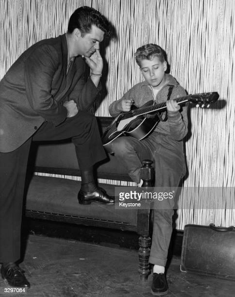 Year-old rock 'n' roll discovery Mike Jackson rehearses for the TV show 'Oh Boy' while American singer-songwriter Conway Twitty listens in. The show...