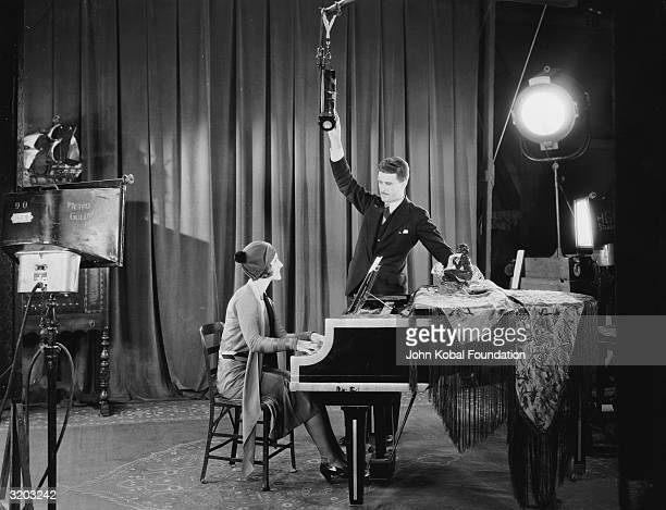 A man adjusts the microphone for Canadian actress Norma Shearer as she sits at a small piano in the MGM studio