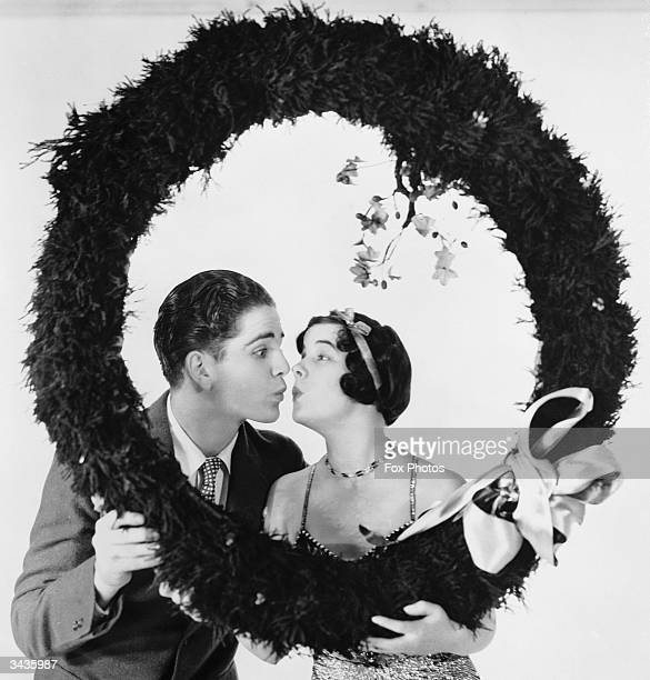 David Sharpe and Gertie Messinger framed inside a wreath of holly to make an appropriate Christmas greeting picture