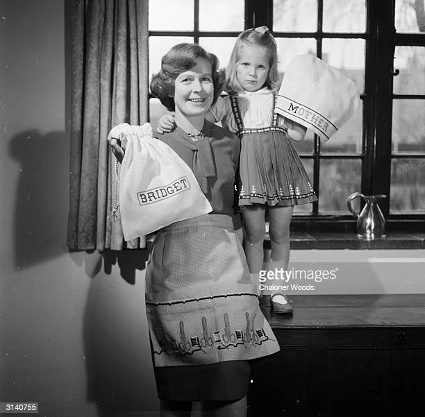 Mother is in an apron embroidered with sewing motifs and her young daughter who is in an embroidered skirt is holding a tea cosy embroidered with the...