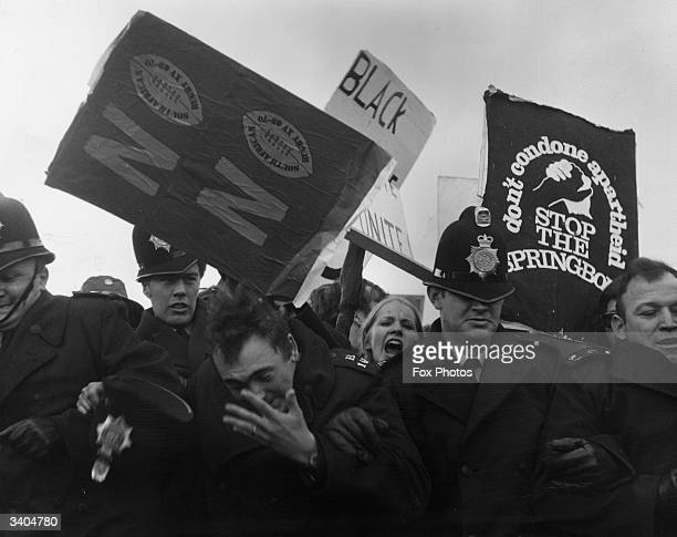 A policeman loses his hat as antiapartheid demonstrators riot at the St Helen's Rugby Ground Swansea Australia during a match between the South...