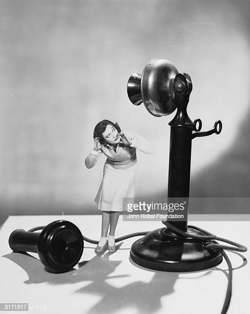 American actress Joan Crawford dwarfed by a giant telephone