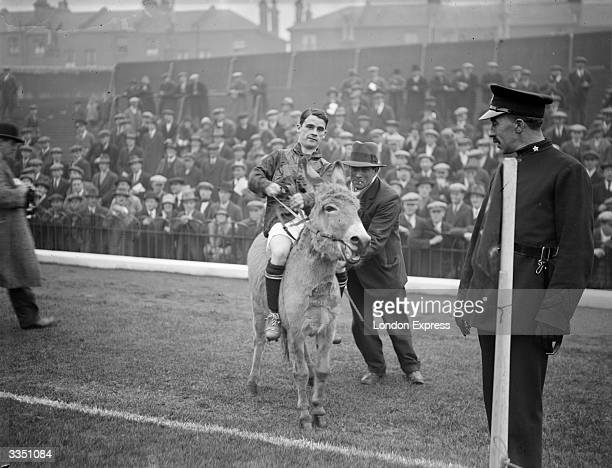 English jockey Sir Gordon Richards riding a donkey at the start of the North v South Country football match at Arsenal FC's ground Highbury in north...