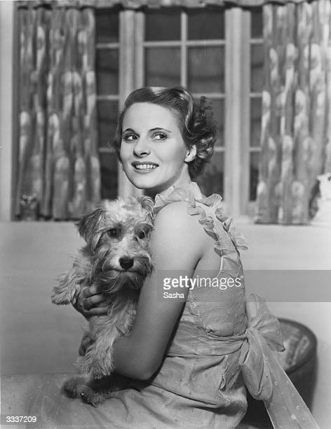 English film actress Ann Todd cuddling a pet terrier in a scene from a production of 'Service' at Wyndham's Theatre London