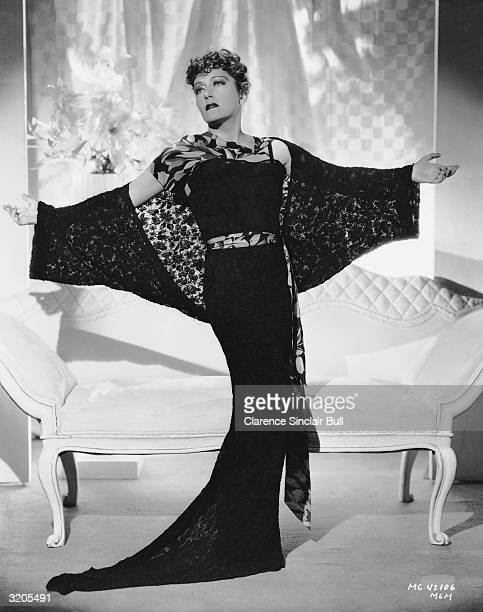 American actress Gloria Swanson spreads out her arms to show off the sheer black lace of her wrap