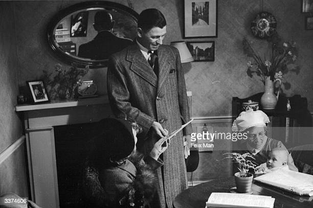 A nurse from the Babies' Hostel Connaught House northwest London run by the National Adoption Society holding a baby in the home of its adoptive...