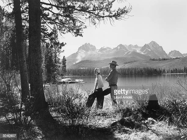 American actor Gary Cooper and his wife 'Rocky' actor Sandra Shaw pose beside the Red Fish Lake in Idaho