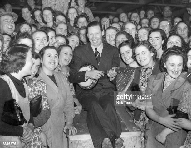 English entertainer George Formby and his ukelele amongst a crowd of war workers during a free concert in the north of England