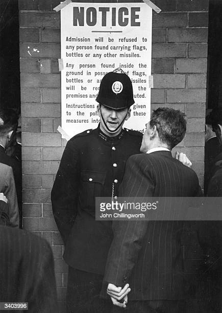 A policemen gives advice to a fan at the local derby football match between Glasgow Rangers and Celtic at the Ibrox stadium in Glasgow Large crowds...