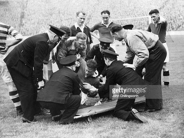Rangers' player is helped off the pitch by ambulance men and Rangers' trainer, Jimmy Smith. The player sustained an injury to his shoulder, during...
