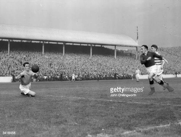 Celtic goalkeeper, Miller, dives for the ball during a Rangers attack, as Celtic play Glasgow Rangers in the Glasgow derby at Ibrox. Large crowds...