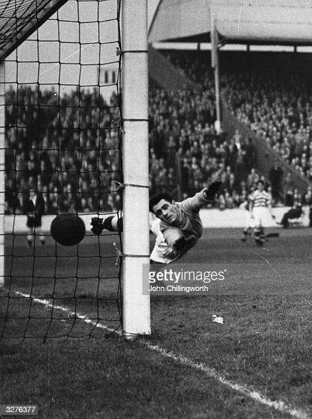 Celtic goalkeeper Miller, fails to keep the ball out of the net during a Glasgow Rangers attack at Ibrox Stadium. Large crowds gather for the matches...