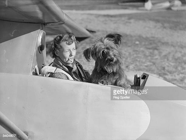 Gliding enthusiast Mrs E E Richardson in the cockpit of a glider with her mascot a Skye terrier