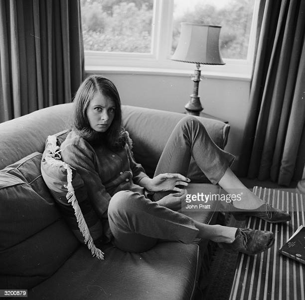 Casually dressed and sitting on a couch with her feet up on a table twenty year old actress Sarah Miles on holiday at her father's home in Cornwall