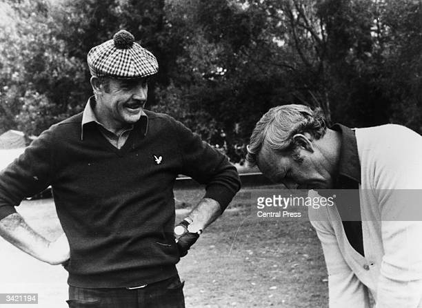 Film star Sean Connery gets a few tips from American golfer Arnold Palmer his partner in a ProAm tournament in Paris