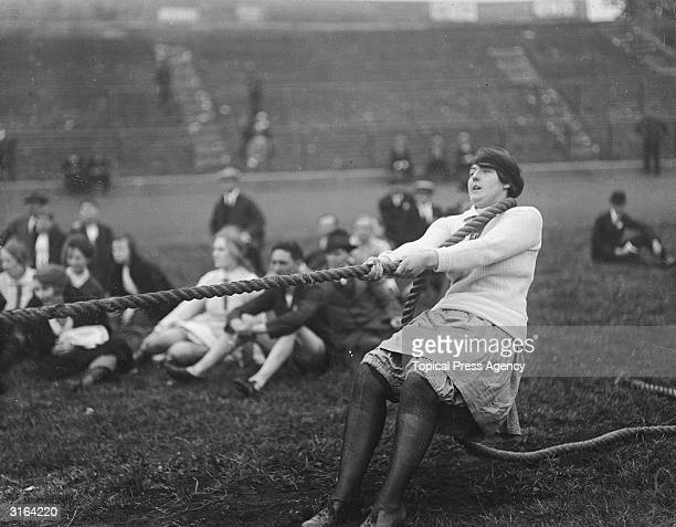 Contestants taking the strain in a tug of war during waitresses sports at Stamford Bridge in Chelsea, London.