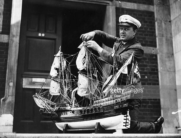 Bus driver Mr L A Stock of Brockley London with his model of the 'Golden Hind' He is adjusting the sails before entering a Model Engineers'...