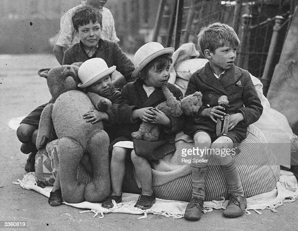 Children clutching toys sit outside their wrecked homes in the morning after an air raid on London