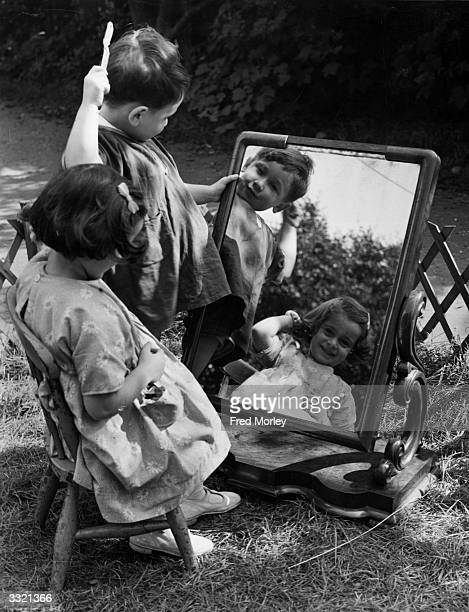 Couple of toddlers grooming themselves in front of a mirror in the garden of the Muriel Green Nursery Centre, in St Albans where women war workers...
