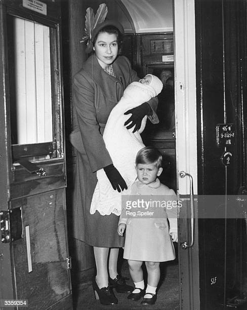 Princess Elizabeth boards a first class railway carriage en route to Balmoral Castle Scotland She is carrying Princess Anne while Prince Charles...