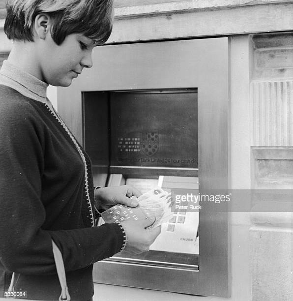 A customer counting out her money after using the world's first cashpoint machine at a London bank