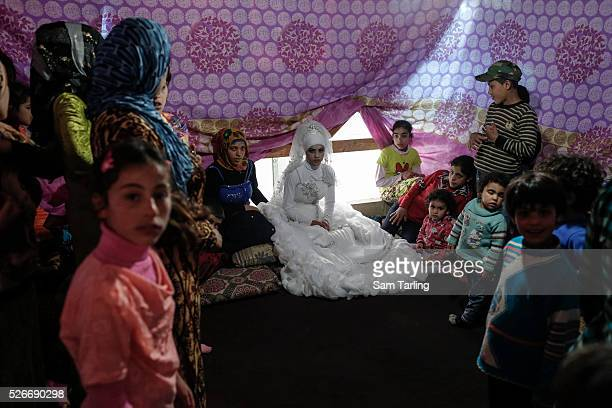 A 15year old newlywedded bride from Damascus Syrian receives well wishers at a Syrian refugee settlement near Tripoli in Lebanon on April 23 2014 The...