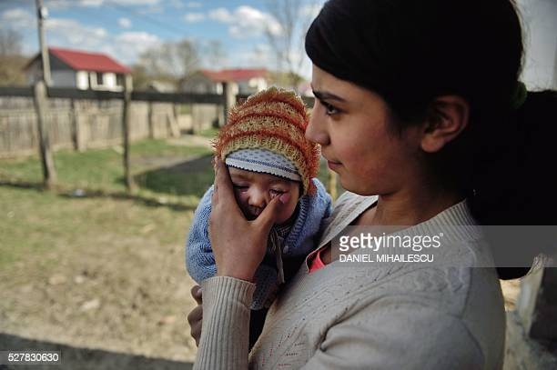 Year-old Diana holds her child at their home in a village near Botosani, north-eastern Romania, on March 30, 2016. In 2013, 15.6 percent of first...